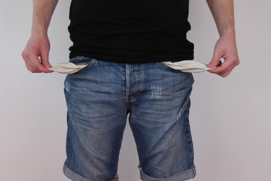 man in jeans showing empty pockets